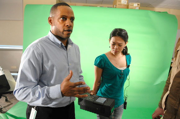 Palmer works with students on the green screen