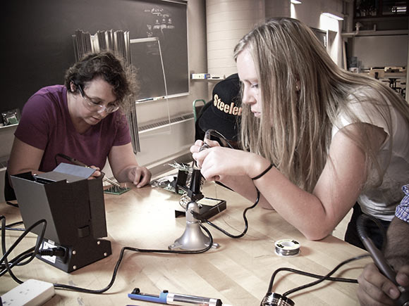 Joan Stanescu (left) and Katelyn Noderer (right), students in Lehigh University�s technical entrepreneurship master�s degree program, work on a soldering assignment during the program�s electronics unit.